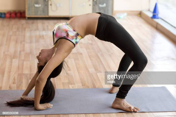 Woman practicing upward bow yoga pose