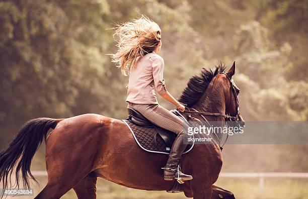 Mulher com o cavalo praticar desporto ao ar livre.