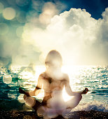 Woman Practicing Yoga by the Sea. Silhouette of a Slim Girl. Nature Background with Sunlight Bokeh. Meditation, Spiritual and Soul Concept. Healthy Lifestyle. Double Exposure Filtered Photo.