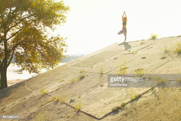 Woman practicing yoga in a concrete construction near a river