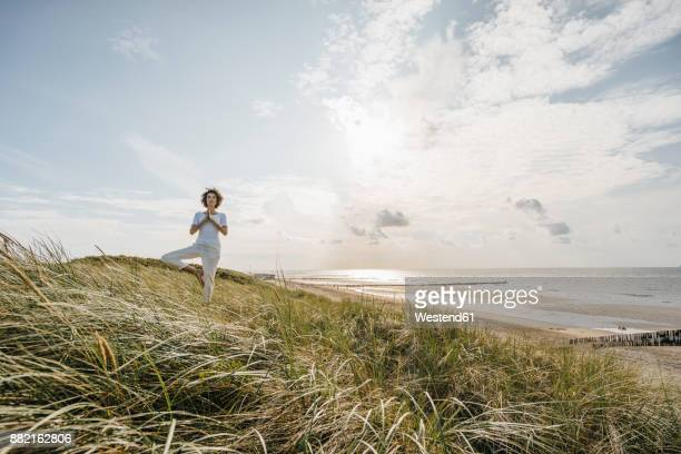 Woman practicing yoga in beach dune