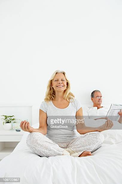Woman practicing yoga in bed with man at the back