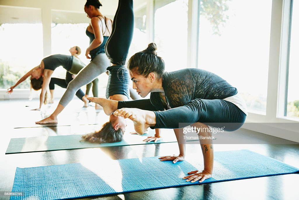 Woman practicing yoga in crow pose during class : Stock Photo