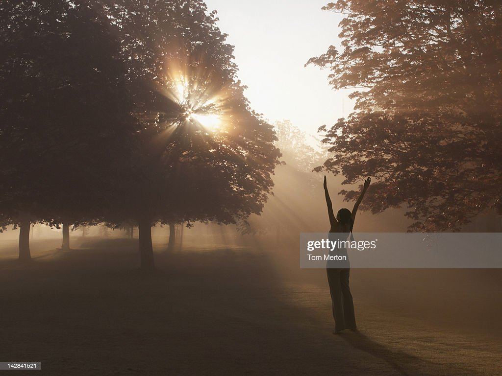 Woman practicing yoga in foggy field : Stock Photo