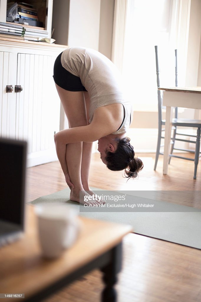 Woman practicing yoga in living room : Stock Photo