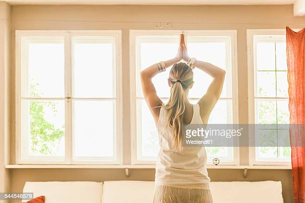 Woman practicing yoga in living room