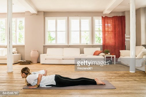 Woman practicing yoga in living room foto stock getty images for Living room yoga sessions