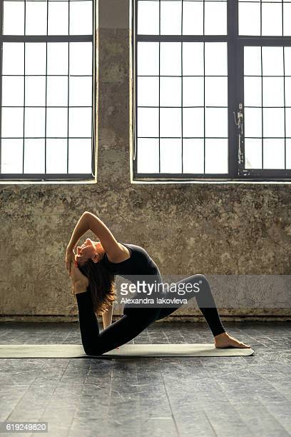 Woman practicing yoga in urban loft: King Pigeon Pose II