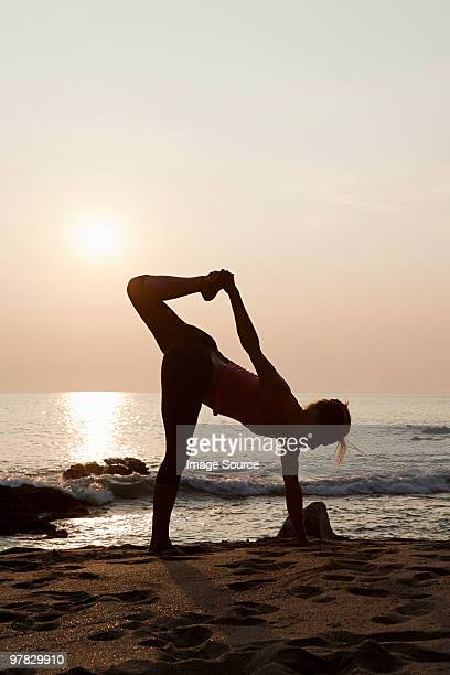 Woman practicing yoga on a beach at sunset