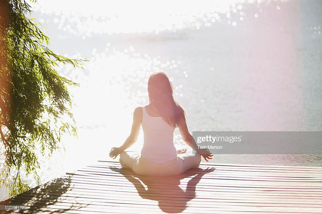 Woman practicing yoga on pier : Stock Photo