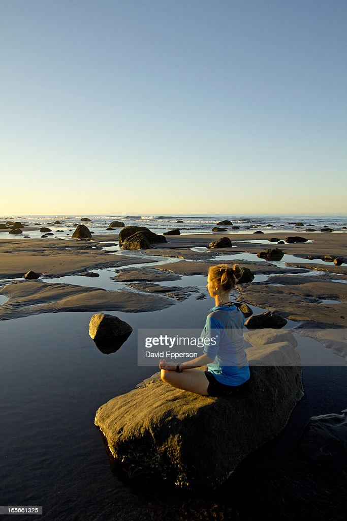 Woman practicing yoga on rock in New Zealand