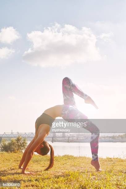 Woman practicing yoga on the grass near the river