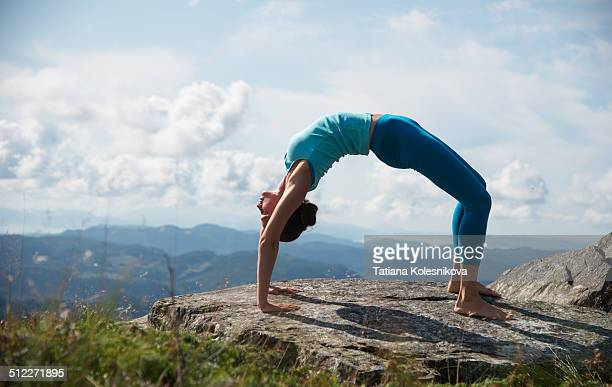 Woman practicing yoga on top of a mountain