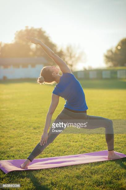 Woman practicing yoga outdoors - Urdhva Virabhadrasana II pose