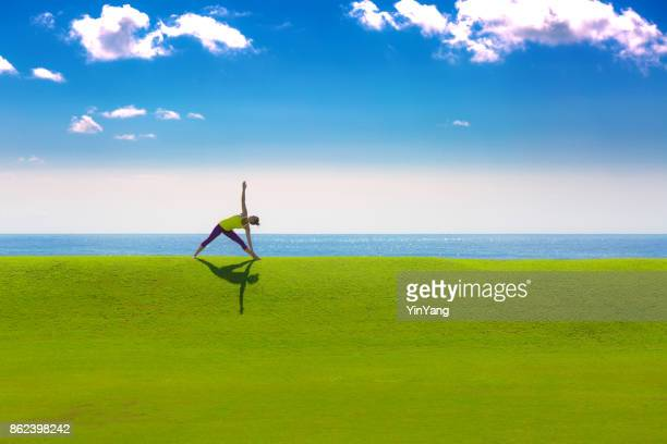 Woman Practicing Yoga Triangle Pose by the Sea in nature