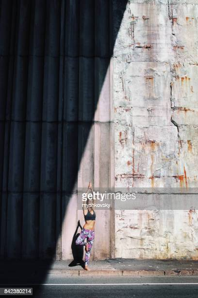 Woman practicing yoga under a bridge
