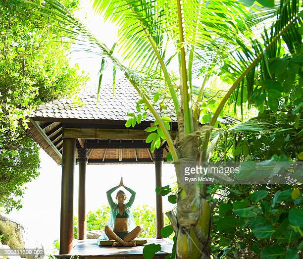 Woman practicing yoga under gazebo, eyes closed