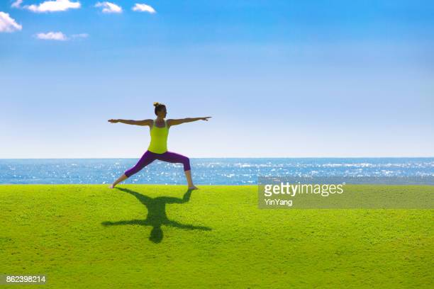 Woman Practicing Yoga Warrior II Pose by the Sea in nature