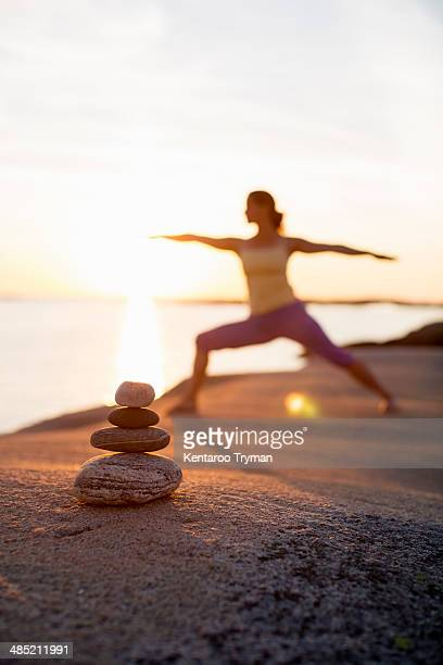 Woman practicing yoga warrior pose on lakeshore with focus on stack of stones