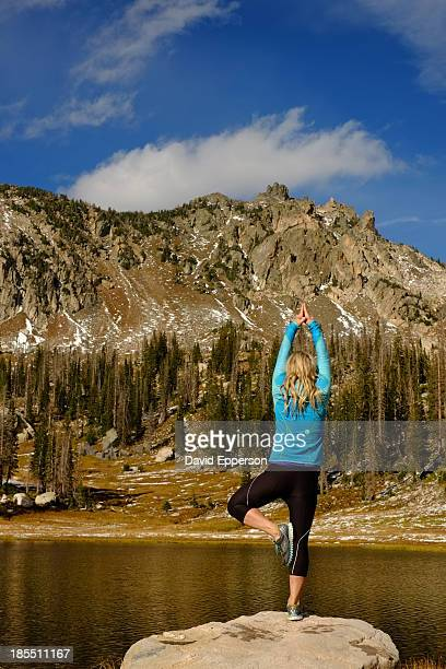 Woman practicing yoga/meditation by alpine lake