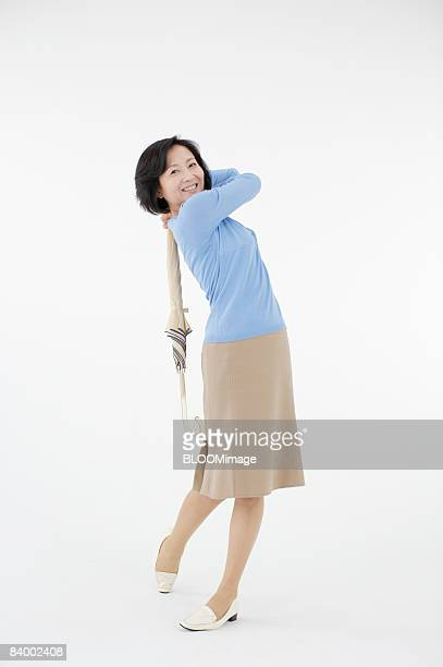 Woman practincing golf swing with umbrella, studio shot