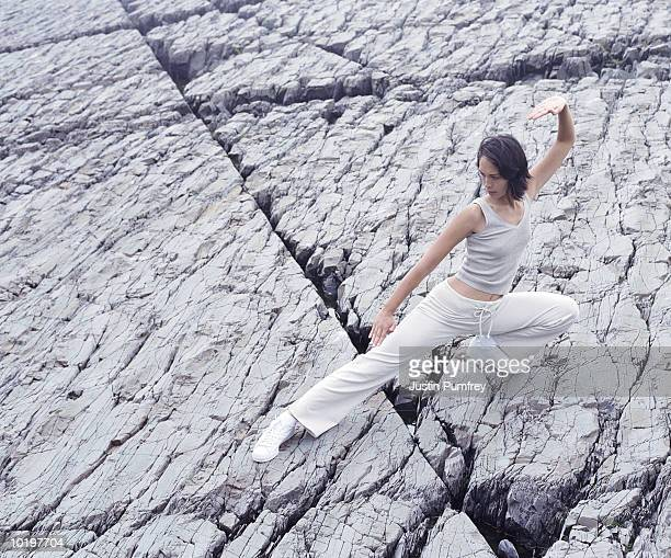 Woman practising kung fu on rock, elevated view