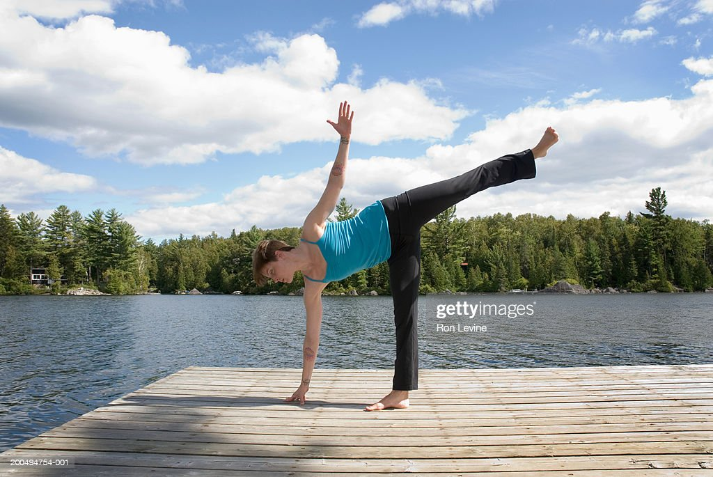 Woman practising yoga 'half moon position' on jetty by lake, profile