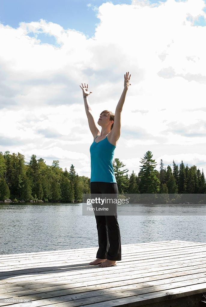 Woman practising yoga 'sun salutation' pose on jetty by lake