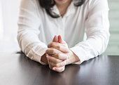 Woman prayer's hands holding together praying in for religious holy spirit, forgiveness, mourning in silence concept