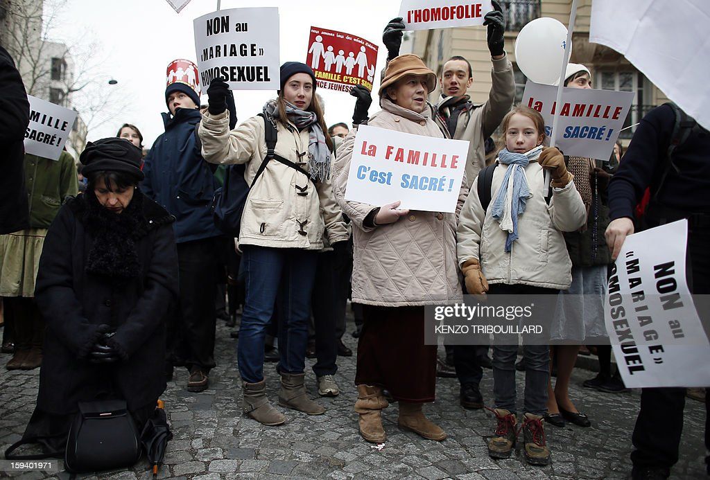 A woman prays as people hold placards reading 'Family is sacred!' during a protest organized by fundamentalist Christians group Civitas Institute against same-sex marriage on January 13, 2013 in Paris. Tens of thousands march in Paris on January 13 to denounce government plans to legalise same-sex marriage and adoption which have angered many Catholics and Muslims, France's two main faiths, as well as the right-wing opposition. The French parliament is to debate the bill -- one of the key electoral pledges of Socialist President -- at the end of this month.