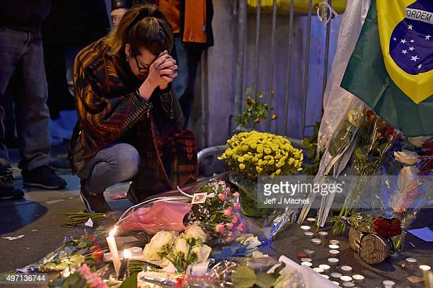 A woman prays as people place flowers and candles on the pavement near the scene of yesterday's Bataclan Theatre terrorist attack on November 14 2015...