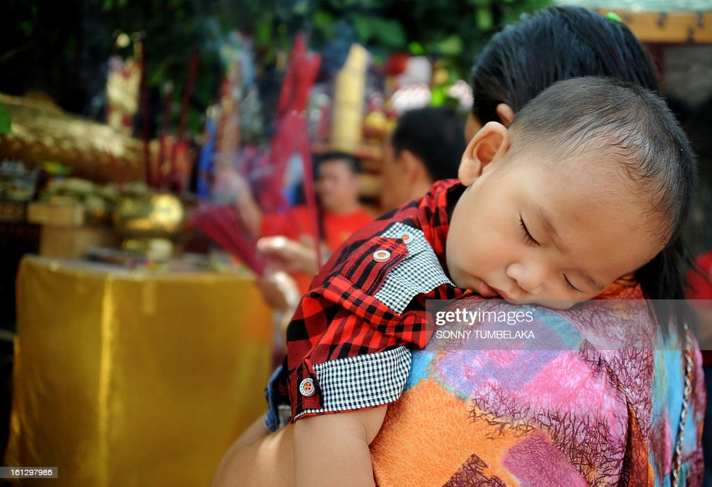 A woman prays as she holds her baby boy to celebrate the Chinese Lunar New Year of the Snake at a Dharmayana temple in Kuta on Indonesia's resort island of Bali on January 10, 2013. Lunar New Year is celebrated in many parts of the predominantly Islamic country of 240 million people where Chinese heritage took roots through ancient transmigration. AFP PHOTO / Sonny TUMBELAKA