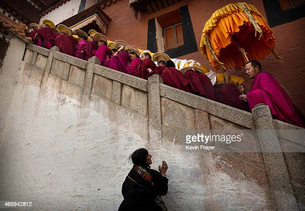 A woman prays as Tibetan Buddhist Monks of the Gelug or Yellow Hat order carry a large thangka of Buddha after showing it to worshippers during...