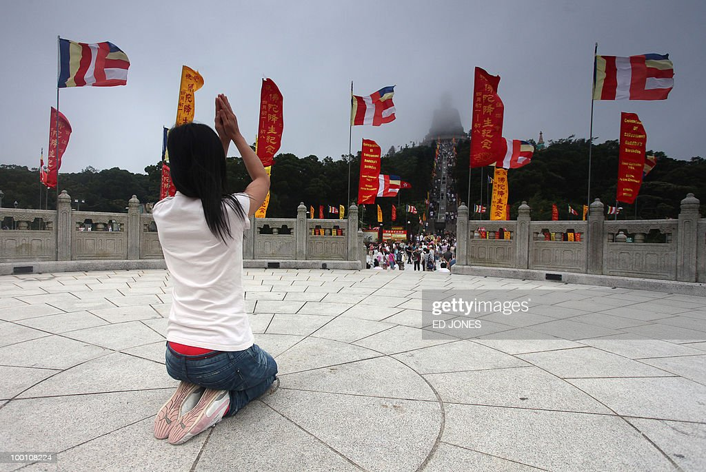 A woman prays before the Tian Tan Buddha