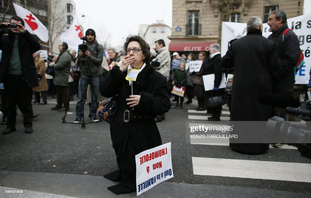 A woman prays during a protest organized by fundamentalist Christians group Civitas Institute against same-sex marriage on January 13, 2013 in Paris. Tens of thousands march in Paris on January 13 to denounce government plans to legalise same-sex marriage and adoption which have angered many Catholics and Muslims, France's two main faiths, as well as the right-wing opposition. The French parliament is to debate the bill -- one of the key electoral pledges of Socialist President -- at the end of this month.