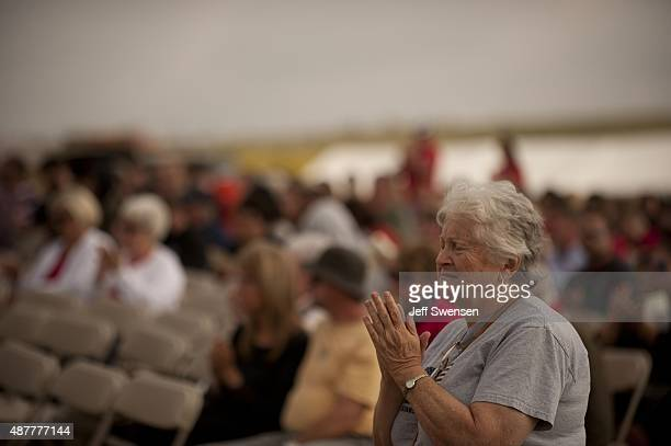 A woman prays during services at the Flight 93 National Memorial during the 14th anniversary of the 9/11 attack in Shanksville Pennsylvania Homeland...