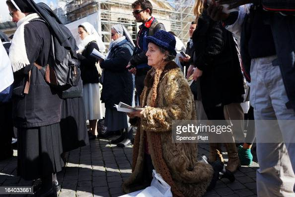 A woman prays during the Inauguration Mass for Pope Francis in St Peter's Square on March 19 2013 in Vatican City Vatican The mass is being held in...