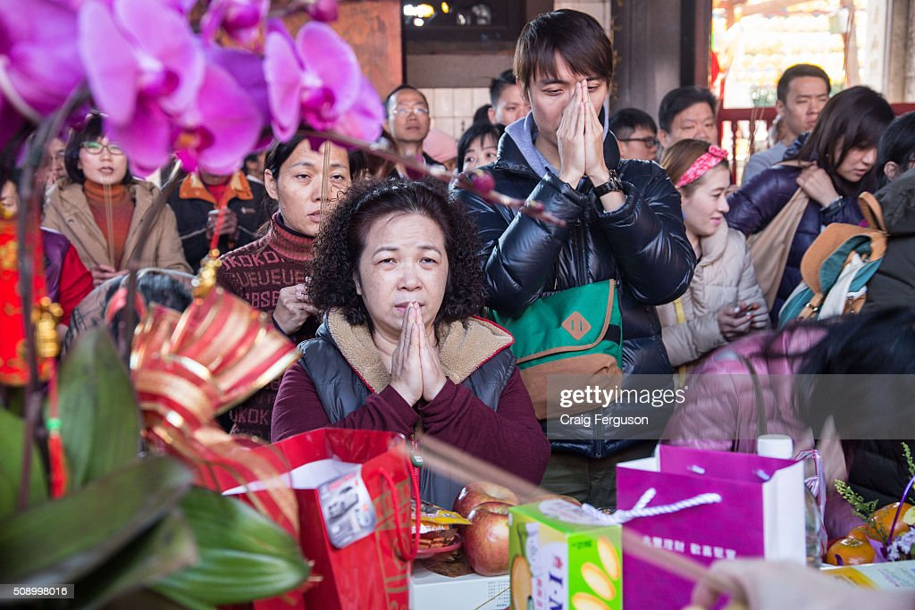 A woman prays for new year blessings as the year of the monkey begins. On the first day of the Chinese lunar year it is traditional to visit temples to light incense and pray for a prosperous year. Thousands come to Longshan Temple, one of the oldest and most important in Taipei every year.