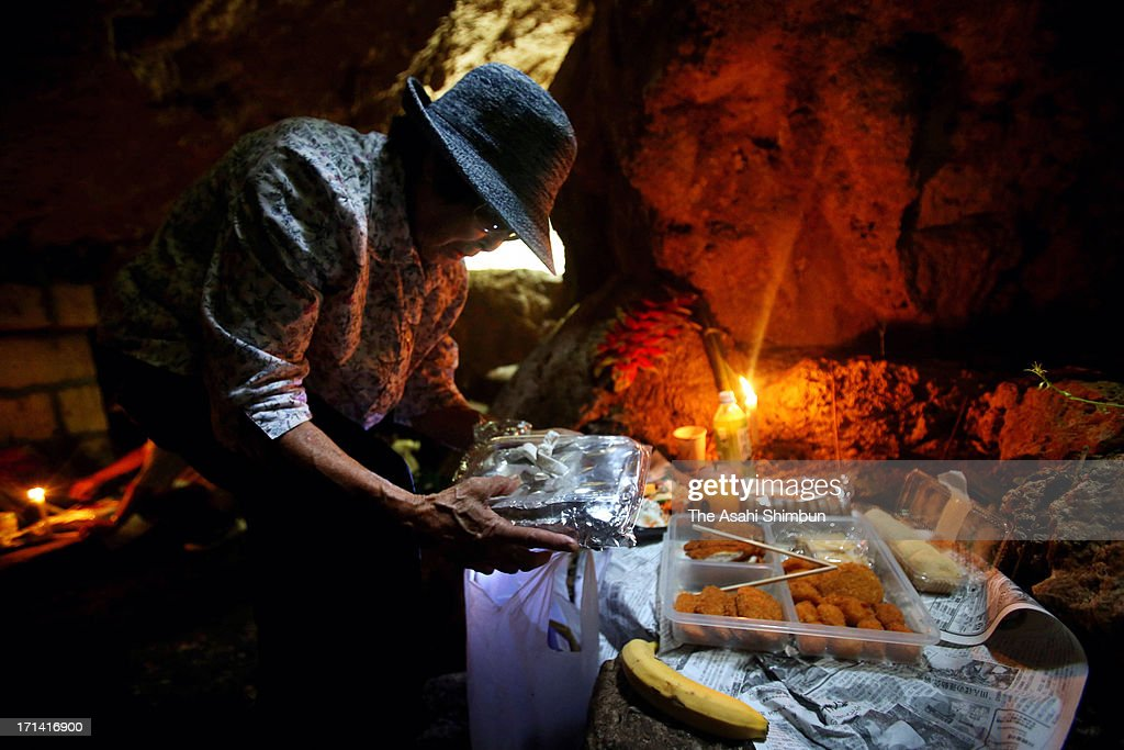 A woman prays for the war dead at 'Gama', the cave used as the evacuation place during the Battle of Okinawa, on June 23, 2013 in Itoman, Okinawa, Japan. During the 3-month ground battle at the end of World War II, more than 200,000 people were killed.