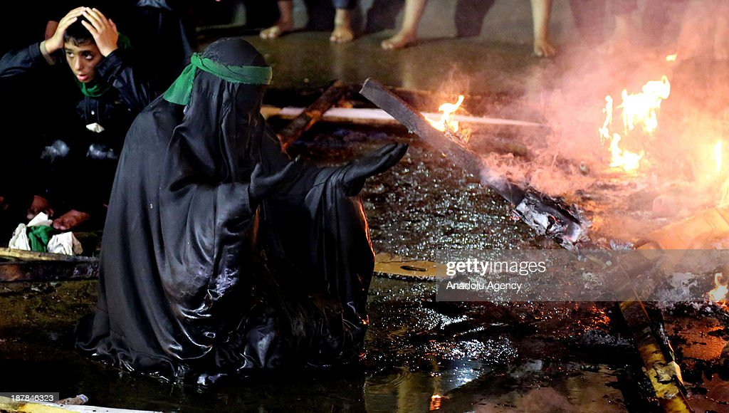 A woman prays front of a fire according to a ritual ceremony of the Ashura Dayon November 13, 2013 in Karbala, Iraq. Muslims to celebrate the day of Ashura which is the tenth day of Muharram (the first month of the Islamic calendar), mourning the seven-century martyrdom of Prophet Mohammad's grandson Prophet Hussein (Husayn ibn Ali) who was killed in Battle of Karbala in Iraq 680 AD.