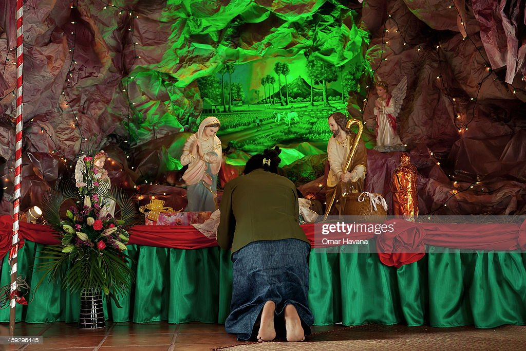 A woman prays in front of a Nativity scene inside the church of Our Lady of the Assumption on December 25, 2013 in Battambang, Cambodia. The parish at Battambang dates back to 1790 when the Catholic community first arrived. Now they serve around 1000 Catholics and 600 families.