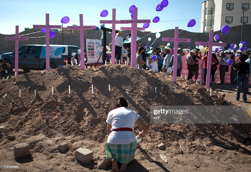 A woman prays in front of crosses during the passage of the 'caravan of comfort' along Ciudad Juarez Chihuahua state Mexico on June 10 2011 A Mexican...