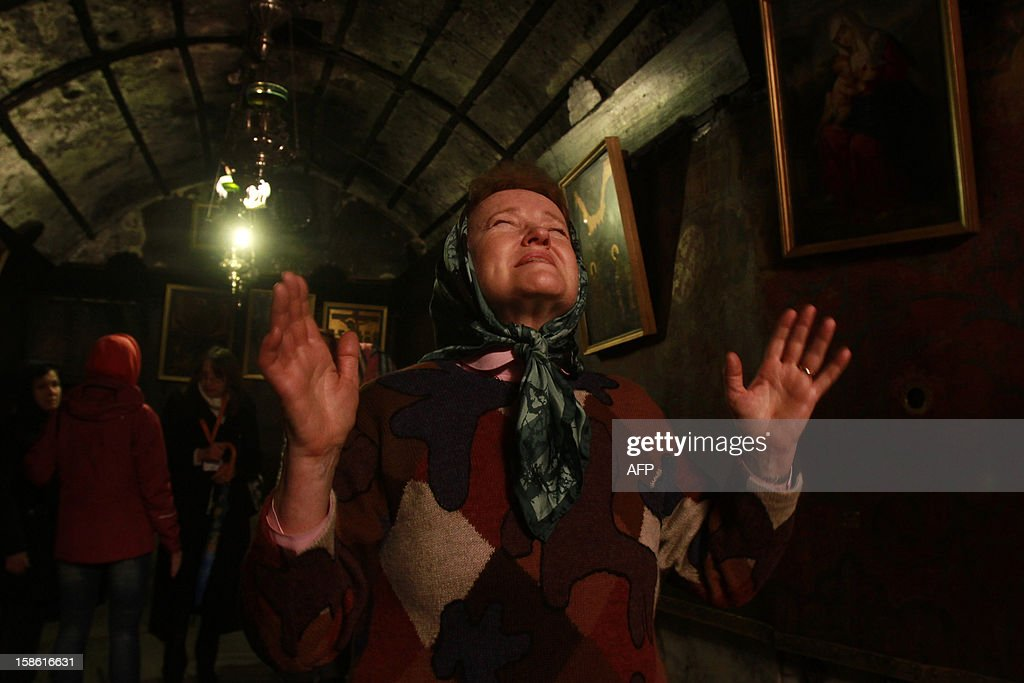 A woman prays inside the Grotto where Christians believe the Virgin Mary gave birth to Jesus Christ in the Church of the Nativity, in the West Bank biblical town of Bethlehem, the traditional birthplace of Jesus as preparations for Christmas celebrations get underway on December 21, 2012.
