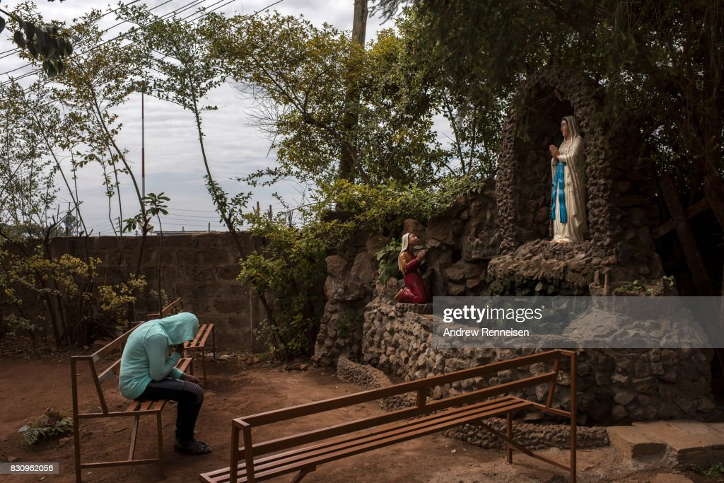 A woman prays inside the grounds of Our Lady of Guadalupe Parish in the Kibera slum on August 13, 2017 in Nairobi, Kenya. A day prior, demonstrations turned violent in some areas throughout Kenya after Uhuru Kenyatta was named to his second term in Kenya's 2017 presidential election.