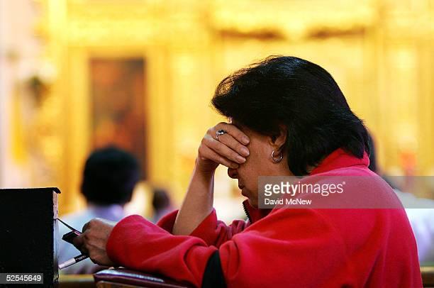A woman prays inside the Iglesia de la Placita at Nuestra Senora Reina de Los Angeles or Our Lady Queen of Angeles Church March 31 2005 in Los...