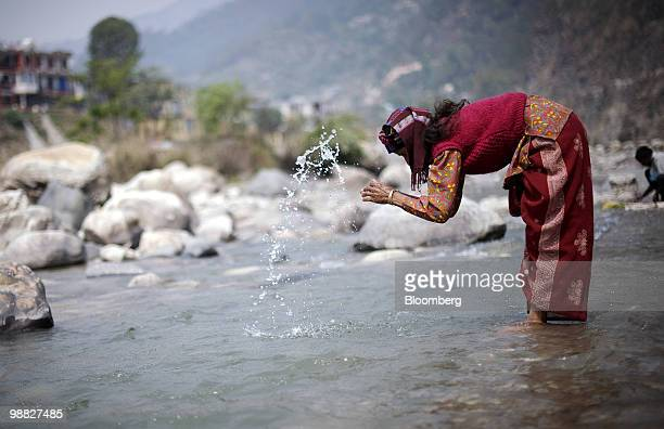 A woman prays near the site of a proposed dam along the Ganges River in the town of Uttarksahi Uttarkhand India on Thursday April 8 2010 The Indian...