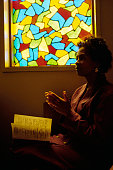 A woman prays next to a stained glass window in the aftermath of the 1992 riots in Los Angeles Residents are trying to recover from the chaos and...