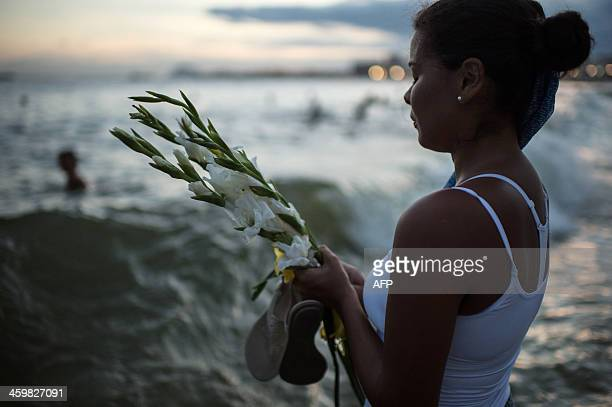 A woman prays to the Yoruba goddess of the sea Yemanja at Copacabana beach in Rio de Janeiro Brazil on December 31 2013 AFP PHOTO / YASUYOSHI CHIBA