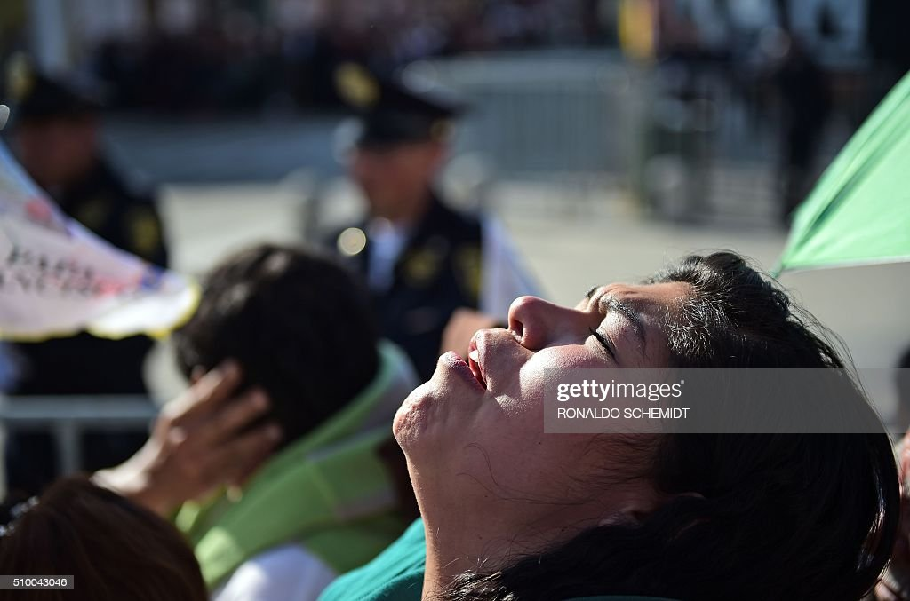 A woman prays whilst waiting for the arrival Pope Francis at the Guadalupe Basilica in Mexico City on February 13, 2016. Pope Francis urged Mexican bishops Saturday to take on drug trafficking with 'prophetic courage,' warning that it represents a moral challenge to society and the church. AFP PHOTO / RONALDO SCHEMIDT / AFP / RONALDO SCHEMIDT