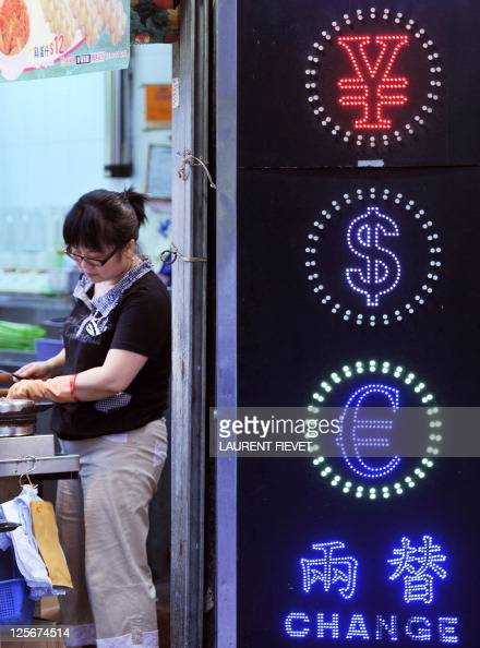 A woman prepares a dish at her shop next to a currency exchange sign in Hong Kong on September 15 2011 Hong Kong said it has no plans to unpeg its...